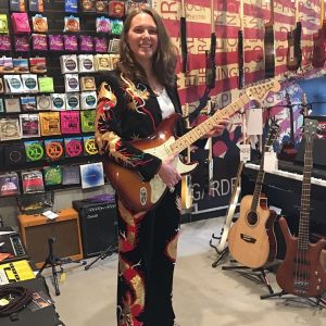 Woman Holding Guitar in the Garden Music School