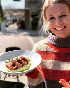 Woman Presenting a Meal from Chef's Table at the Edgewater & The Tasting Room
