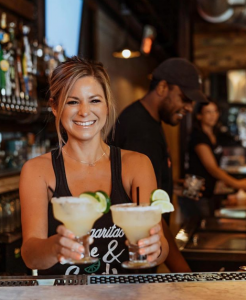 Smiling Waitress Serving Drinks at The Whole Enchilada
