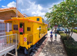 Cyclists Riding by the Train Caboose on the West Orange Trail