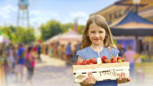 Young Girl Holding a Basket of Strawberries at the Farmers Market