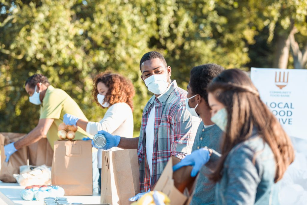 A mid adult man places a canned food item into a paper bag as he volunteers with his teenage son at an outdoor food bank. He and other volunteers are wearing protective face masks as they are volunteering during the coronavirus pandemic.